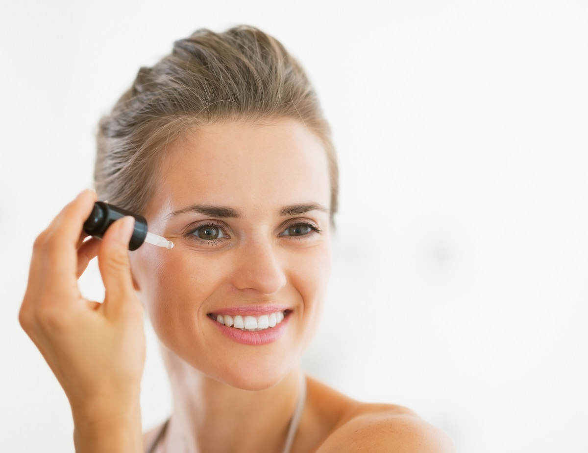 Portrait of happy young woman applying cosmetic serum